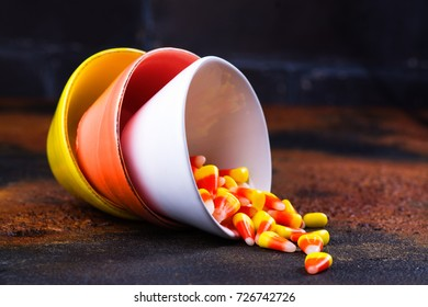Traditional Halloween sweets - candy corn in bright colorful bowls on dark background. Space for text