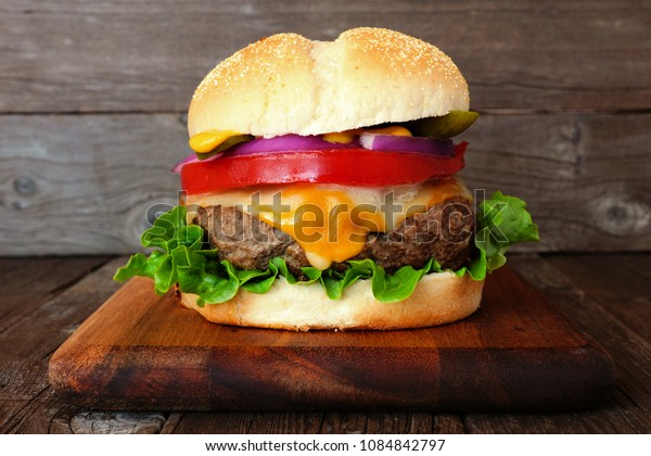 Traditional hamburger with cheese, lettuce, tomato and onion on a serving board with wood background