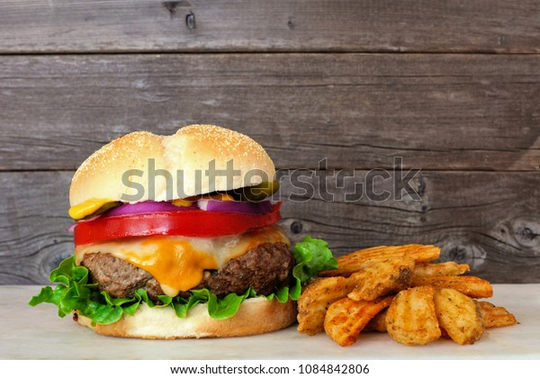 Traditional hamburger with potato wedges against a rustic wood background