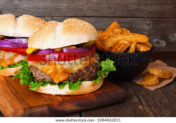 Traditional hamburgers with potato wedges on a serving board with wood background