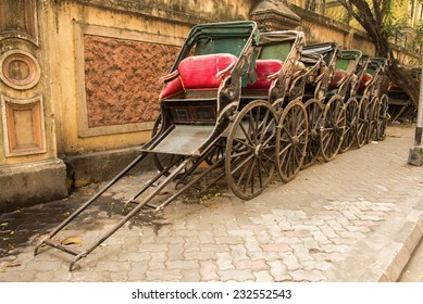 Traditional hand pulled Indian rickshaws parked together in front of a old building in Kolkata