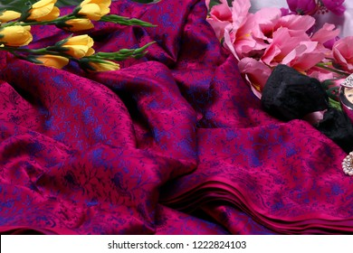 Traditional handmade black, redpink Indian silk sari saree with golden details, woman use to wear on Onam festival, Vishu, wedding or in party in  India. Close up of stack of multi-colored saree