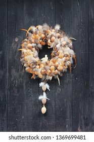 Traditional handmade wreath with eggs, feather and figure of bird for easter, outside on the door, Europe.