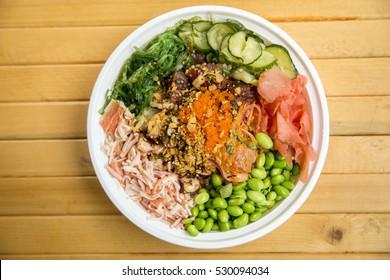 Traditional Hawaiian Ahi and Salmon Poke Bowl with Seaweed, Edamame, Pink Ginger, Cucumber, Fish Roe and Fresh Crab