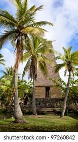 A traditional Hawaiian hut and palm trees in Polynesian Cultural Center Oahu Hawaii