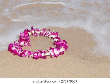 A traditional, Hawaiian lei made of pink and white orchids in a heart shape on a beach in Hawaii