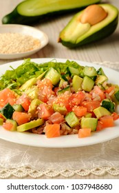 Traditional hawaiian raw salmon poke bowl with avocado, cucumber, tomato, sesame seeds, lettuce and rice in bottom. Vertical view. Vegetables on the background.