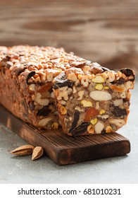 Traditional healthy fruit cake with nuts for on wooden board over black slate background
