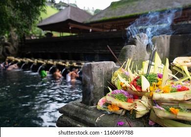 Traditional hindu balinese offerings as flowers, money and food in a basket in Tirta Empul temple, Hindu water temple, Bali, Indonesia
