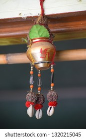 A traditional hindu swastik symbolized vessel with a coconut having beads with a holy  Rudraksh hanging on door , specially used in a sense of blessing from God and good luck for family.