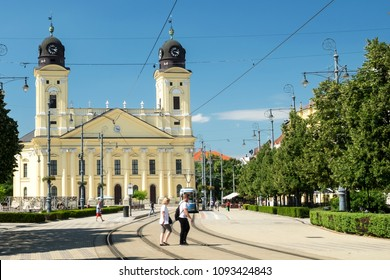 The traditional historical architecture, the walking people on weekend promenade and the old tram - public transport of Debrecen, the popular spa resort town in Hungary