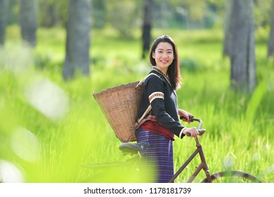 Traditional Hmong girl with basket of agricultural crops walking with bicycles in forest Happy Hmong girl smiling with green nature in Sapa city, northern Vietnam