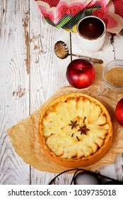 Traditional holiday apple pie. Baked dessert with anise, cloves and apples on light wooden background