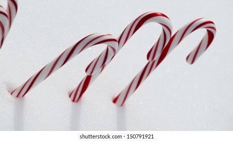 Traditional holiday candy candy cane in snow.