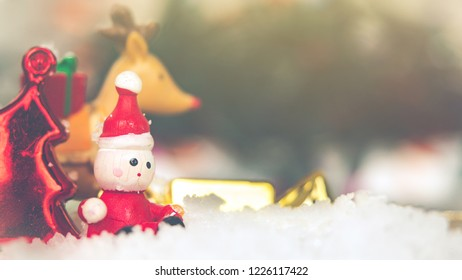 Traditional holiday decorations Concept. Close-up of Santa Claus made form wooden sitting on snow between colorful Christmas decoration and blurred Christmas tree with sunlight. Vintage style.