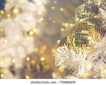 Traditional holiday decorations Concept. Close-up golden ball for Christmas decoration hang on  white Christmas tree with sunlights. : Filtered process and vintage style.