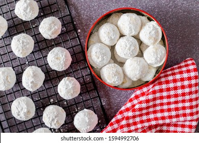 Traditional holiday snowball cookies in cookie gift tin with red and white checkered napkin and additional cookies on wire rack