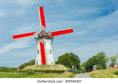 Traditional Holland windmill with red wings in Damme, small village near Bruges, Belgium