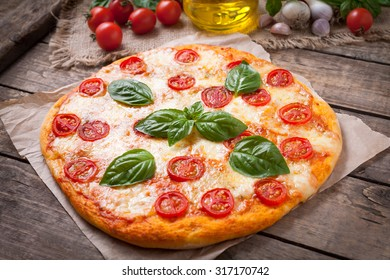 Traditional homemade baked Italian pizza margherita with mozzarella basil and tomatoes on vintage wooden table background. Rustic style and natural light.
