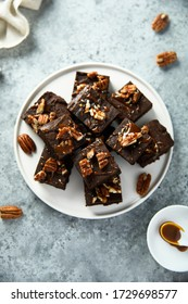 Traditional homemade brownies with salted caramel and pecan nuts