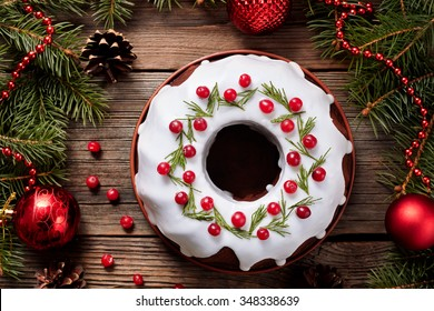Traditional homemade christmas cake holiday dessert with cranberry in new year tree decorations frame on vintage wooden table background. Rustic style. Top view