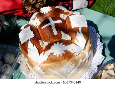 Traditional homemade decorated Serbian Easter bread on green table and pieces of bread representing Jesus body, outdoor on sunny day