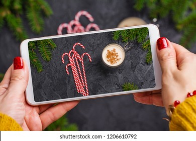 Traditional homemade eggnog drink. Woman with xmas red manicure taking photo of egg nog drink in a glass cup on mobile phone. Trendy instagram photo shot. Copy space. Top view, flat lay style