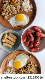 Traditional homemade Filipino brunch food including eggs, breakfast sausage (longanisa), rice with fried pork jowls (sisig) and vegetables, and spring rolls (lumpia)