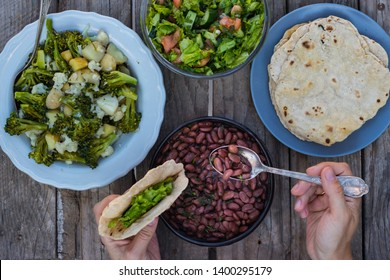 Traditional homemade food. Spicy red beans, flat pita bread (puri, chapati, roti) with fresh summer salad on wooden table. Woman hands holds vegan lunch or vegetarian dinner. Top above view