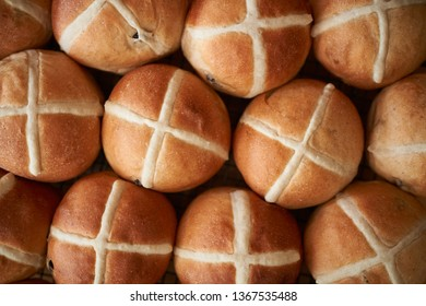 Traditional homemade fruit bread, freshly made Hot Cross Buns cooling down on a baking rack ready to celebrate Easter Weekend.