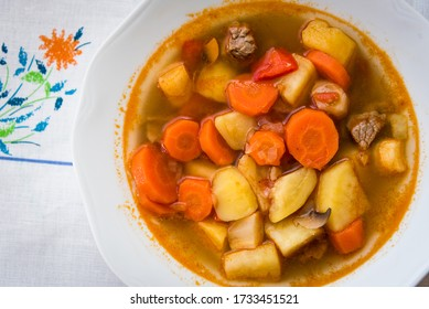 Traditional homemade Hungarian hot goulash soup with mear, potato, carrot and mushrooms in a white plate on the table. European cuisine. Top view.