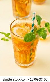 Traditional homemade iced tea with lemon, mint and ice in tall glasses. Summer cold drink on yellowe background. Healthy summer food concept. Selective focus, copy space.