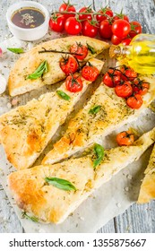 Traditional  homemade Italian flat bread focaccia. Focaccia with tomatoes and basil leaves, wooden background, top view