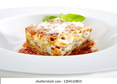 Traditional Homemade Italian Lasagna with Tomato Sauce Isolated on White Background. Hot Tasty Lasagna or Lasagna with Parmesan Cheese on Elegant Restaurant Plate Close Up