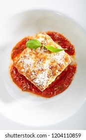 Traditional Homemade Italian Lasagna with Tomato Sauce Isolated on White Background. Hot Tasty Lasagna or Lasagna with Parmesan Cheese on Elegant Restaurant Plate Top View