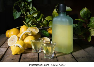 Traditional homemade lemon liqueur limoncello and fresh citrus on the old wooden board. Italian traditional liqueur limoncello with lemon. Italian alcoholic beverage.