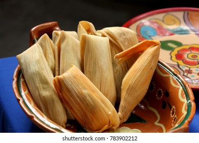 Traditional homemade Mexican food Tamales, Corn dough stuffed with sauce wrapped in corn husk in a clay pot.
