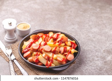 Traditional homemade Peruvian Salchipapa Fries with mayo, ketchup and mustard sauces. French fries with sausages. Fastfood