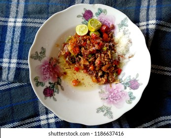 Traditional home-made sambal or can red hot chilles paste. bali traditional sambal. Composition with chili sauce in plate on table. Sambal Indonesian Food.