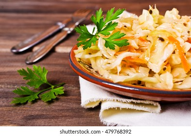 Traditional homemade sauerkraut with carrots, fennel seeds and fresh parsley. Selective focus.