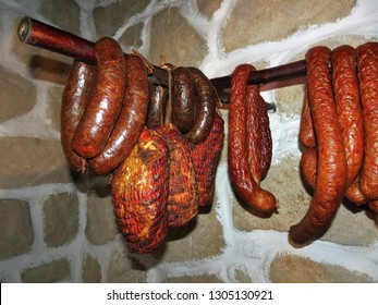 Traditional homemade smoked sausages and ham hang in the pantry, Product of Poland