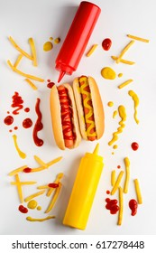 Traditional hot dogs with ketchup and mustard, top-view. French fries, white background, colorful image. Western diet.