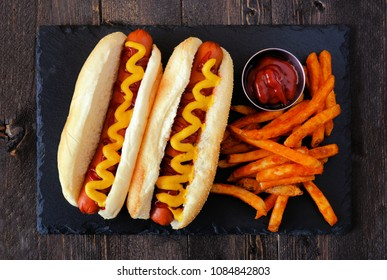 Traditional hot dogs with mustard, ketchup and fries. Top view on a slate server.