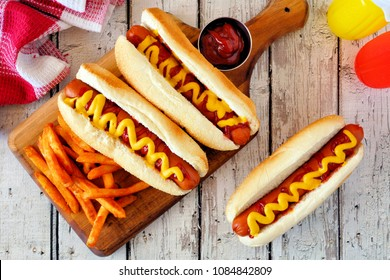 Traditional hot dogs with mustard, ketchup and fries. Top view scene on a white wood background.