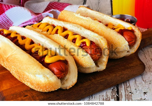 Traditional hot dogs with mustard and ketchup. Close up scene with wood background.