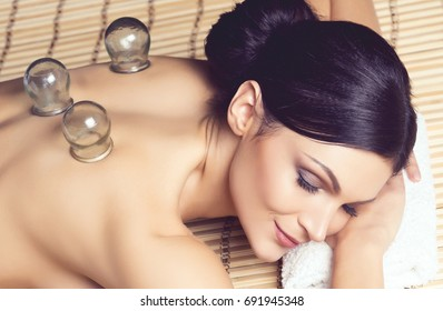 Traditional hot jar cupping massage in spa. Young, beautiful and healthy girl having recreation therapy.