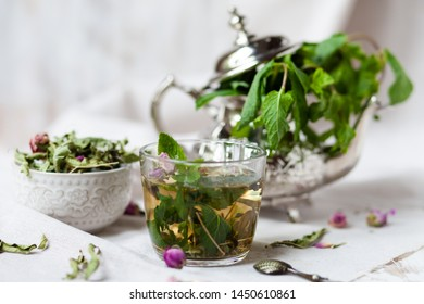 Traditional hot mint moroccan tea served in a transparent cup. Metal teapot with fresh mint on the background. Dry leaves, dry rose flowers and vintage spoon as decor. Gentle detox, natural depressant