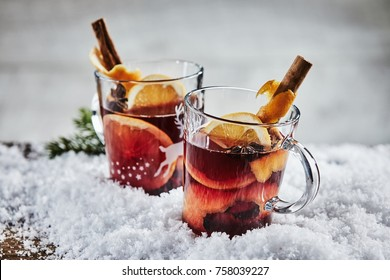 Traditional hot spicy mulled Gluhwein or red wine for Christmas with orange, cinnamon and star anise served in two glass mugs in winter snow
