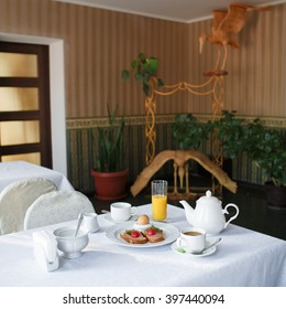 Traditional Hotel Breakfast served at white table with ham and cherry tomato toasts, boiled egg, orange juice and coffee. Morning breakfast with toasts. Warm toning.