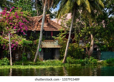 A traditional house is anchored on the shores of a fishing lake in Kerala's Backwaters, India